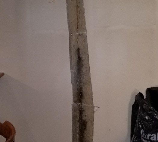Crack in the wall leaking onto the floor of a basement.